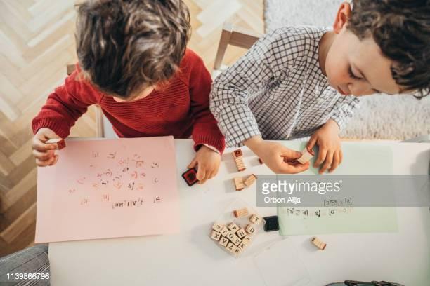 家で描く男の子 - 綴り ストックフォトと画像