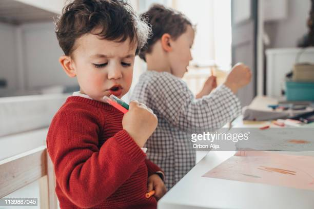 chicos dibujando en casa - niñez fotografías e imágenes de stock