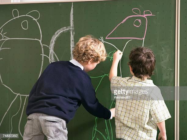 Boys (4-7) drawing on blackboard, rear view