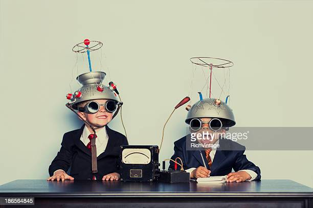 boys dressed as businessmen wearing mind reading helmets - brainstormen stockfoto's en -beelden