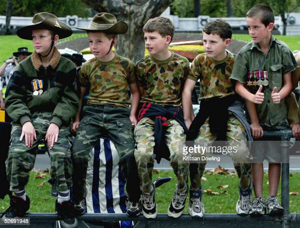Boys dressed in army fatigues look on as the ANZAC Day parade as it makes its way from Flinders Street Station along St Kilda Road to the Shrine of...