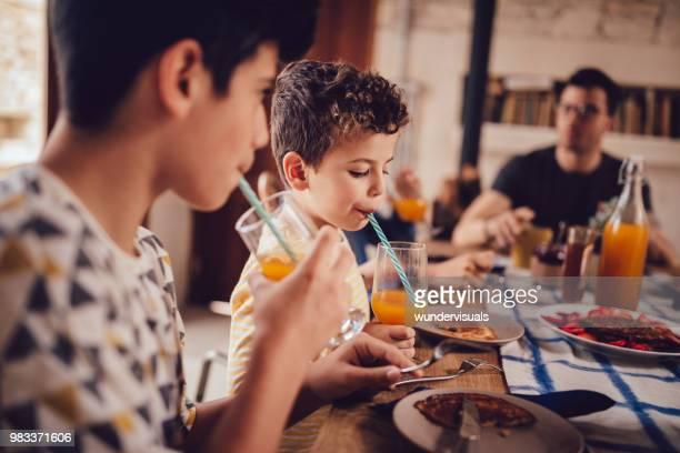 Boys drinking fresh orange juice during breakfast with family