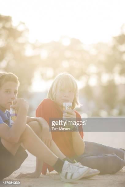 Boys drinking juice outdoors