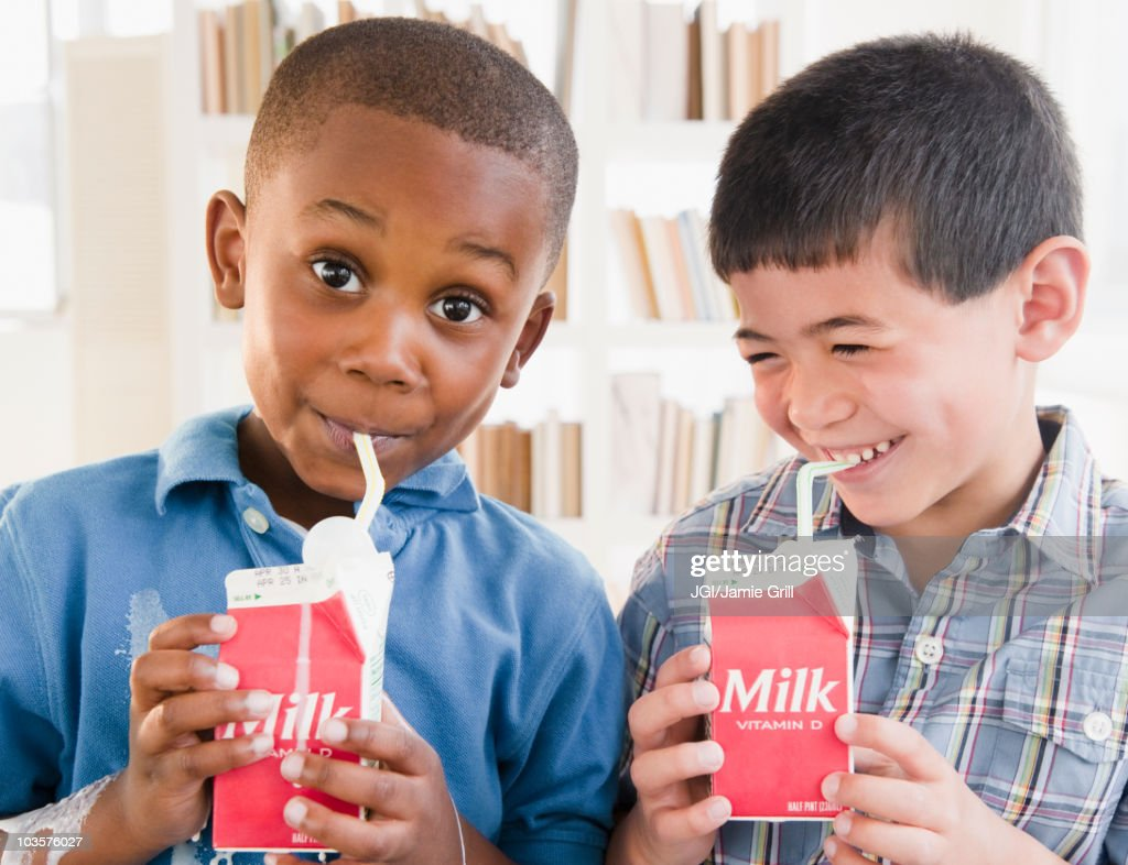 Boys drinking milk from carton : Stock Photo