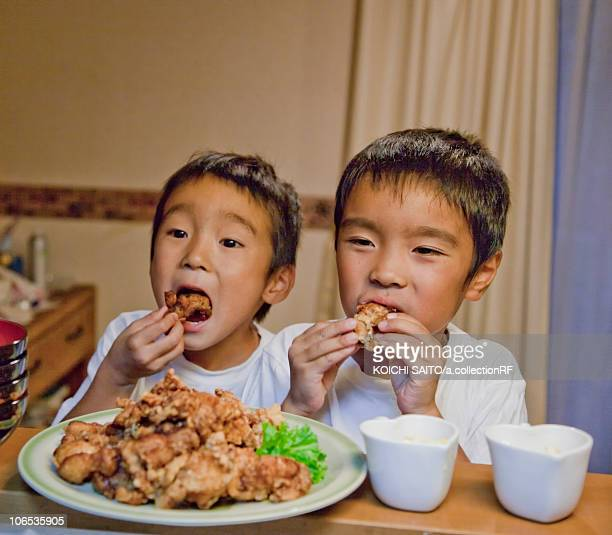 Boys eating fried chicken, Japan