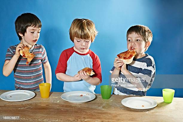 Boys eating pizza at table