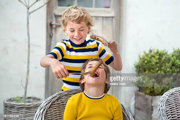 boys eating sausages at a barbecue - nur kinder stock-fotos und bilder