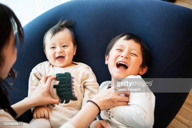boys enjoying being tickled by their mother - 純真 ストックフォトと画像