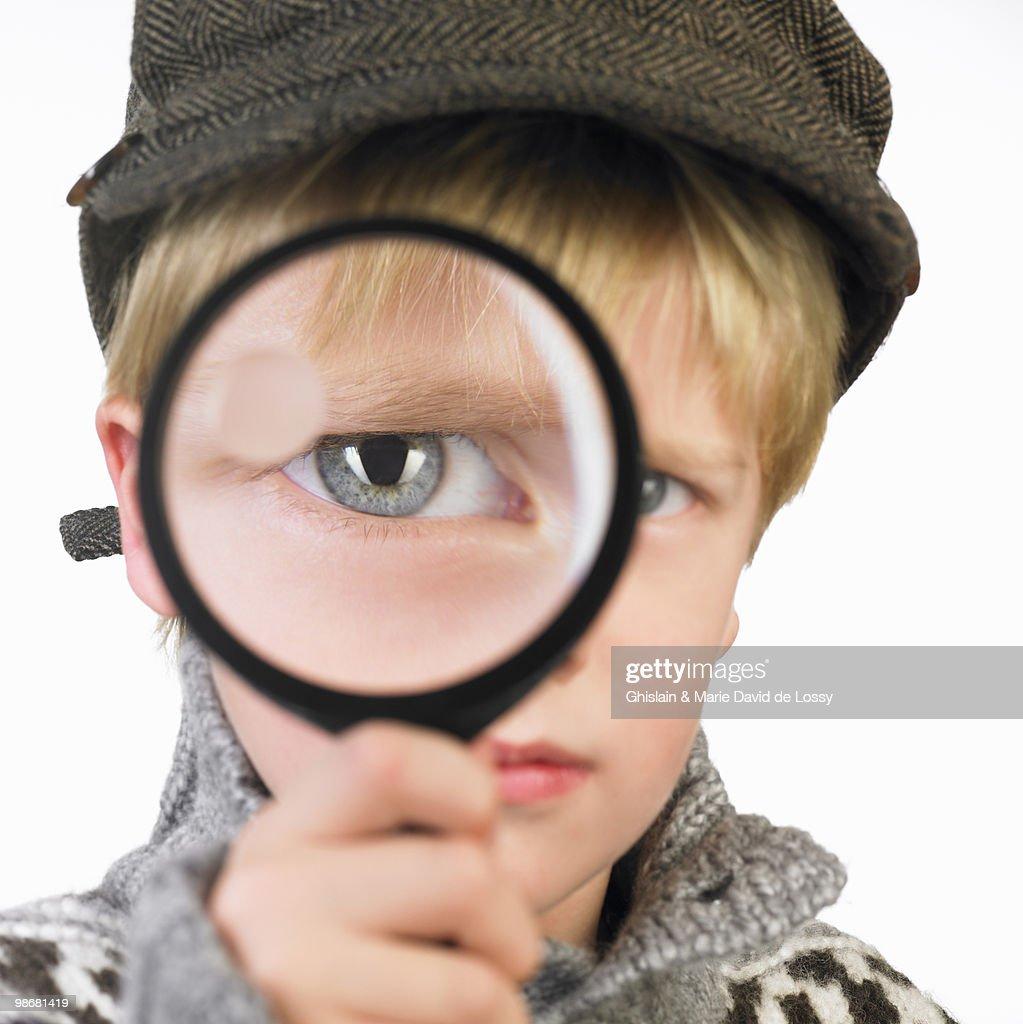 Boy\'s eye through a magnifying glass : Stock Photo