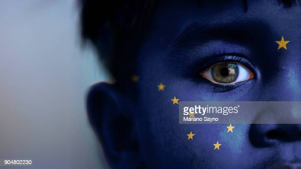 Boy's face, looking at camera, cropped view with digitally placed Alaska State flag on his face.
