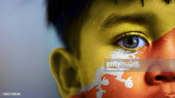 Boy's face, looking at camera, cropped view with digitally placed Bhutan flag on his face.