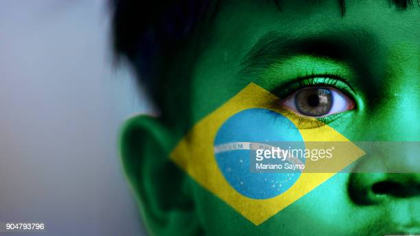 Boy's face, looking at camera, cropped view with digitally placed Brazil flag on his face.