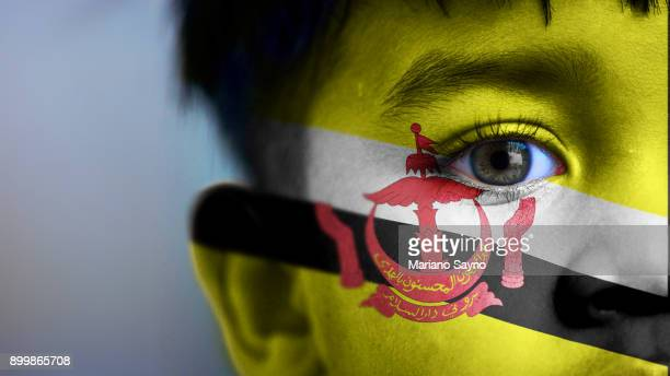 Boy's face, looking at camera, cropped view with digitally placed Brunei flag on his face.