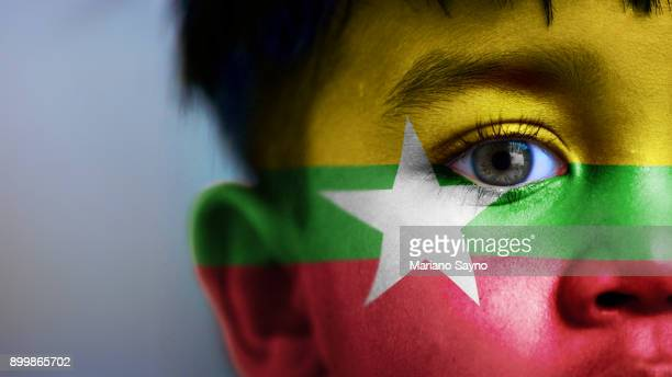 boy's face, looking at camera, cropped view with digitally placed burma flag on his face. - myanmar culture stock photos and pictures