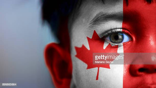 boy's face, looking at camera, cropped view with digitally placed canada flag on his face. - canadian culture stock pictures, royalty-free photos & images