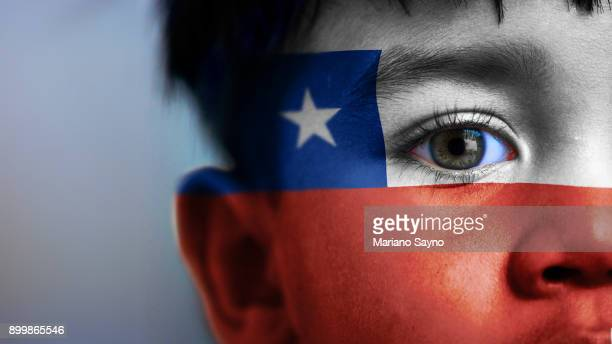 boy's face, looking at camera, cropped view with digitally placed chile flag on his face. - bandiera del cile foto e immagini stock