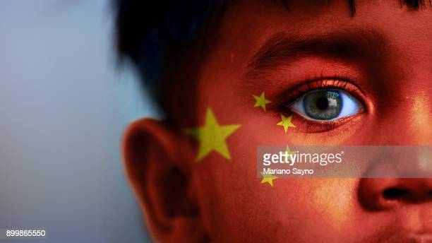 Boy's face, looking at camera, cropped view with digitally placed China flag on his face.