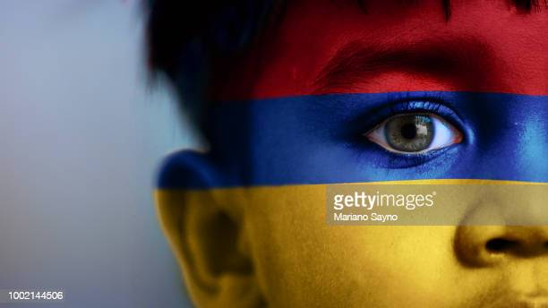 Boy's face, looking at camera, cropped view with digitally placed Armenia flag on his face.