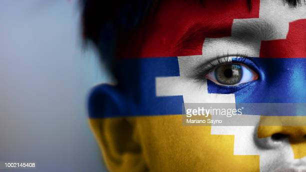 Boy's face, looking at camera, cropped view with digitally placed Artsakh flag on his face.