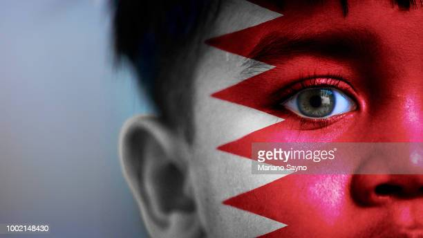 boy's face, looking at camera, cropped view with digitally placed bahrain flag on his face. - bahrain stock pictures, royalty-free photos & images