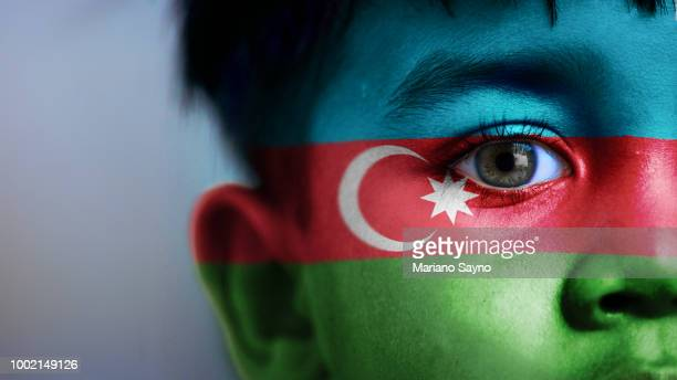 Boy's face, looking at camera, cropped view with digitally placed Azerbaijan flag on his face.