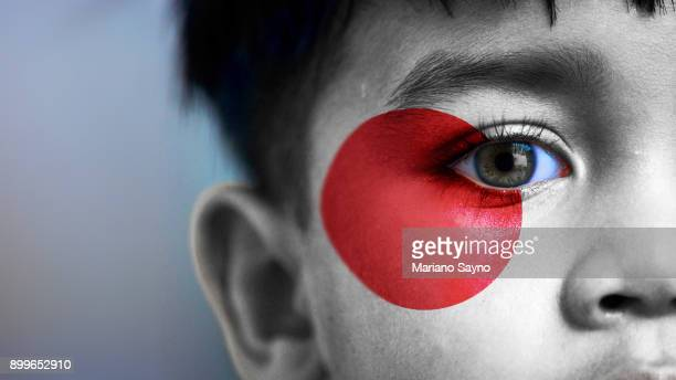 boy's face, looking at camera, cropped view with digitally placed japanese flag on his face. - camera icon stock pictures, royalty-free photos & images