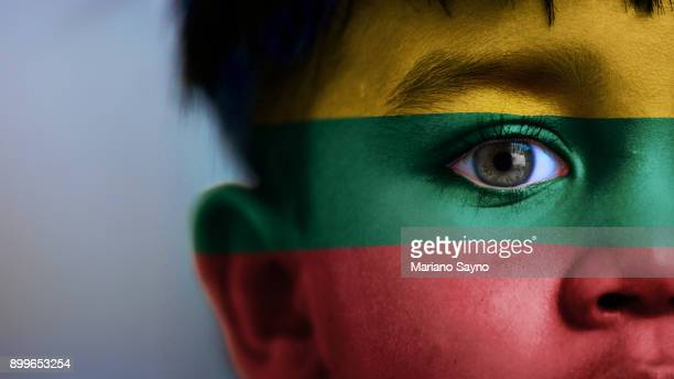 Boy's face, looking at camera, cropped view with digitally placed Lithuania flag on his face.