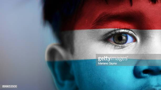 boy's face, looking at camera, cropped view with digitally placed luxembourg flag on his face. - luxemburgo fotografías e imágenes de stock