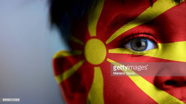 Boy's face, looking at camera, cropped view with digitally placed Macedonia flag on his face.