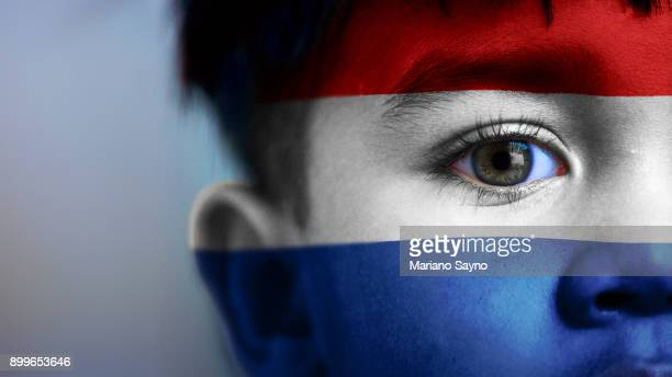 Boy's face, looking at camera, cropped view with digitally placed Netherlands flag on his face.