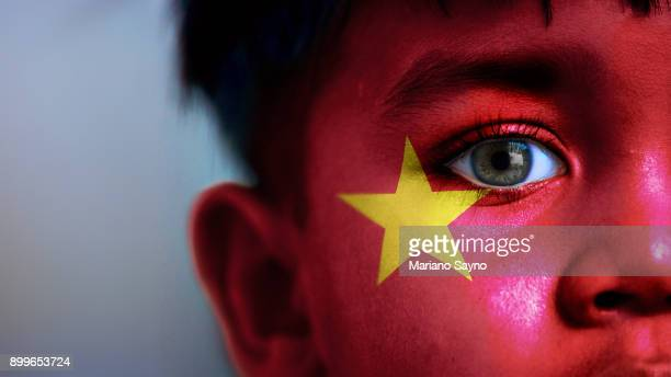 Boy's face, looking at camera, cropped view with digitally placed Vietnam flag on his face.