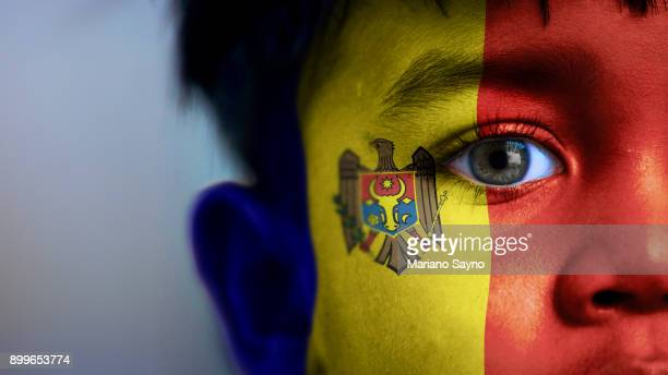 Boy's face, looking at camera, cropped view with digitally placed Moldova flag on his face.