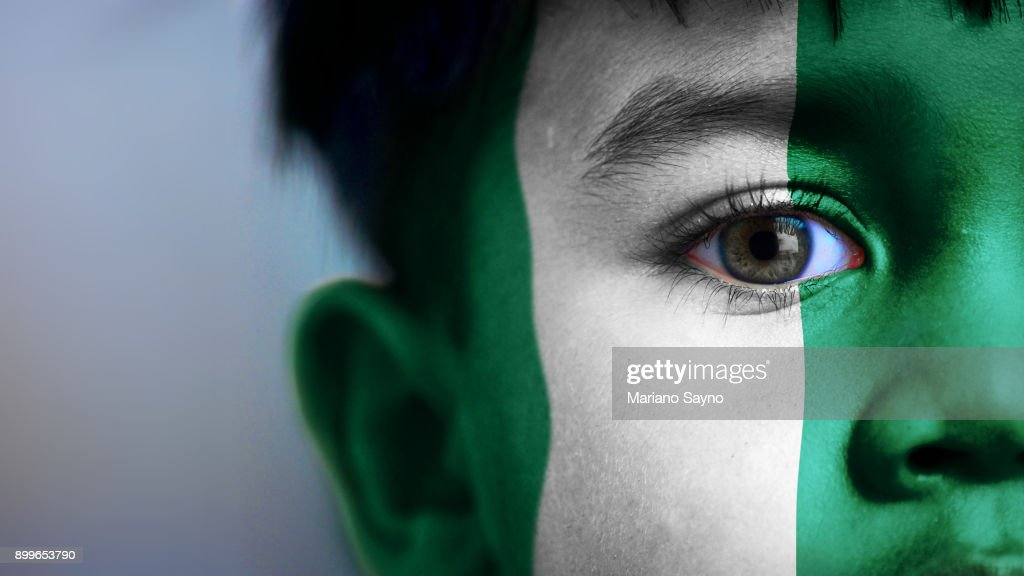 Boy's face, looking at camera, cropped view with digitally placed Nigeria flag on his face.