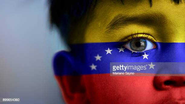 Boy's face, looking at camera, cropped view with digitally placed Venezuela flag on his face.