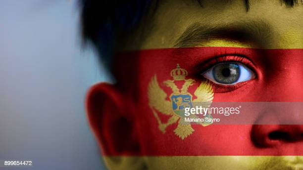 Boy's face, looking at camera, cropped view with digitally placed Montenegro flag on his face.