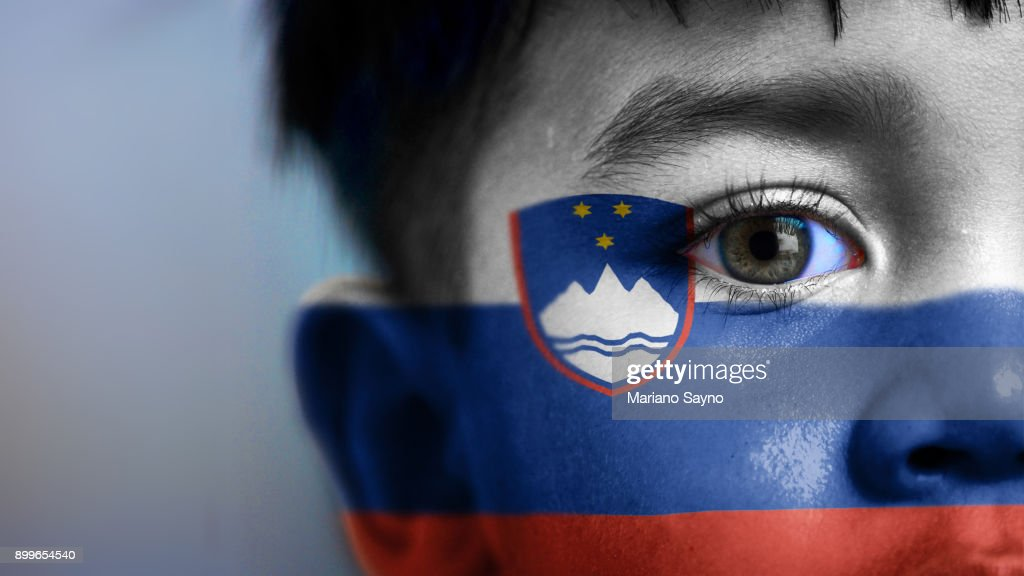 Boy's face, looking at camera, cropped view with digitally placed Slovenia flag on his face. : Stock Photo