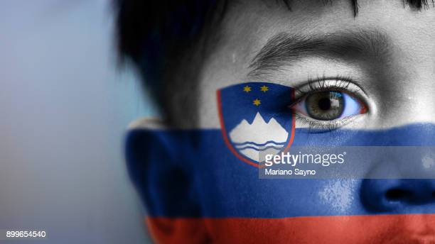 boy's face, looking at camera, cropped view with digitally placed slovenia flag on his face. - スロベニア国旗 ストックフォトと画像