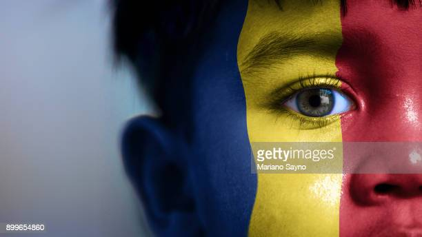 Boy's face, looking at camera, cropped view with digitally placed Romania flag on his face.