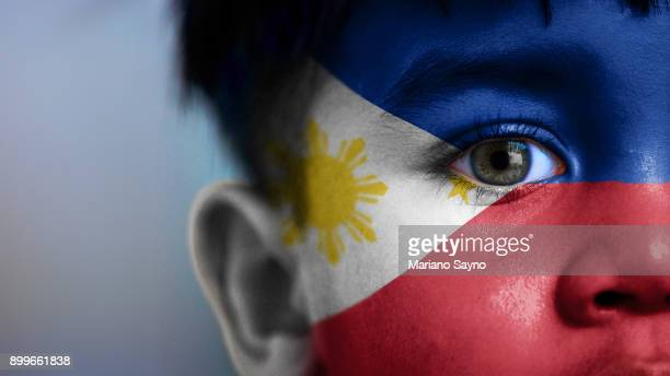 boy's face, looking at camera, cropped view with digitally placed philippines flag on his face. - filipino culture stock pictures, royalty-free photos & images