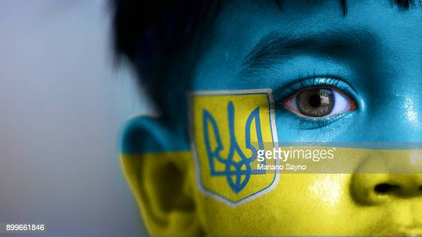 boy's face, looking at camera, cropped view with digitally placed ukraine flag on his face. - ukraine photos et images de collection