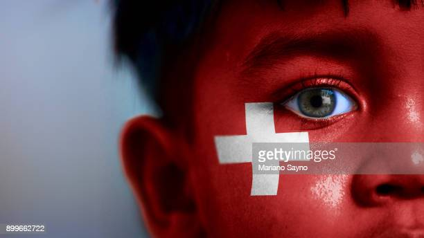 Boy's face, looking at camera, cropped view with digitally placed Switzerland flag on his face.