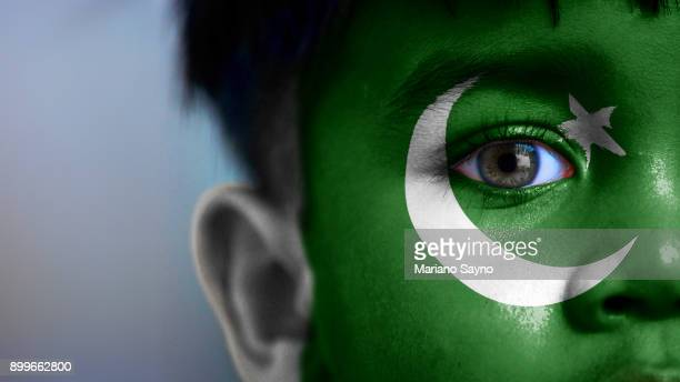 boy's face, looking at camera, cropped view with digitally placed pakistan flag on his face. - pakistani flag stock photos and pictures
