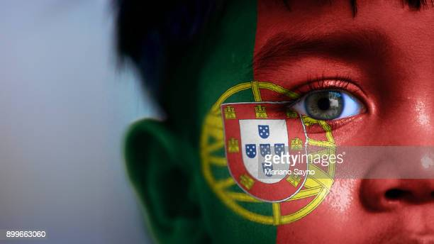 boy's face, looking at camera, cropped view with digitally placed portugal flag on his face. - portugal photos et images de collection