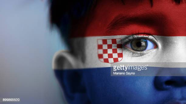 Boy's face, looking at camera, cropped view with digitally placed Croatia flag on his face.
