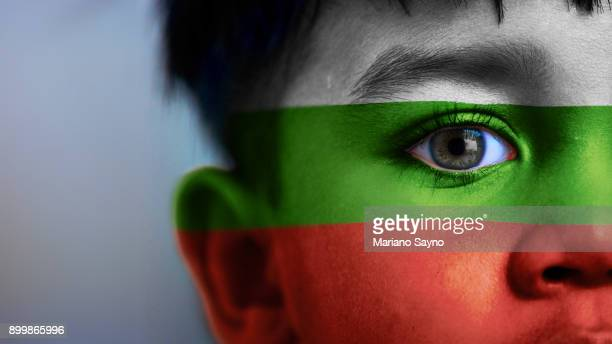 boy's face, looking at camera, cropped view with digitally placed bulgaria flag on his face. - bulgarie photos et images de collection