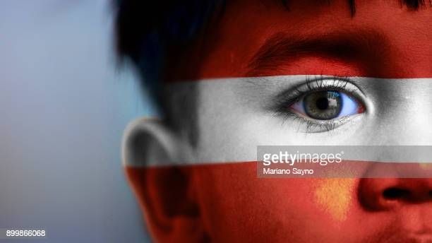 boy's face, looking at camera, cropped view with digitally placed austria flag on his face. - austrian culture stock pictures, royalty-free photos & images