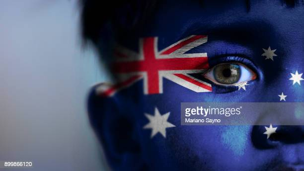 boy's face, looking at camera, cropped view with digitally placed australia flag on his face. - australian flag stock pictures, royalty-free photos & images