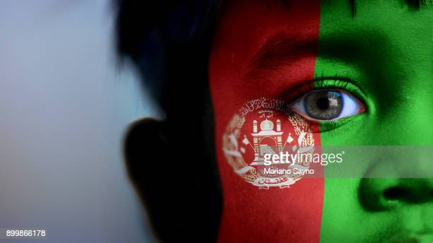 boy's face, looking at camera, cropped view with digitally placed afghanistan flag on his face. - afghanistan war stock-fotos und bilder