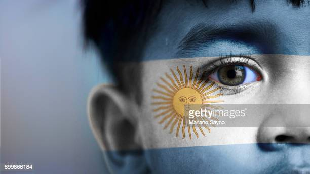 boy's face, looking at camera, cropped view with digitally placed argentina flag on his face. - argentinas flagga bildbanksfoton och bilder