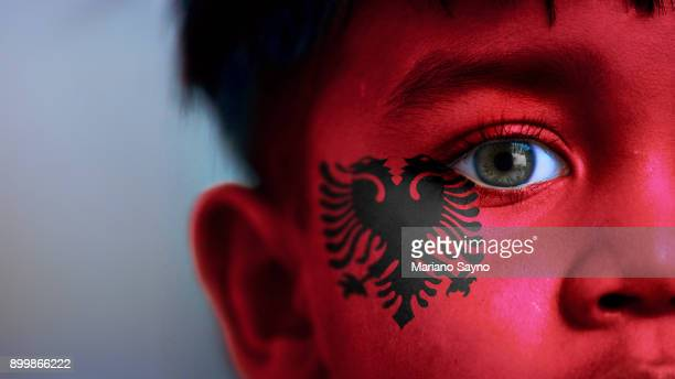 boy's face, looking at camera, cropped view with digitally placed albania flag on his face. - bandiera albanese foto e immagini stock